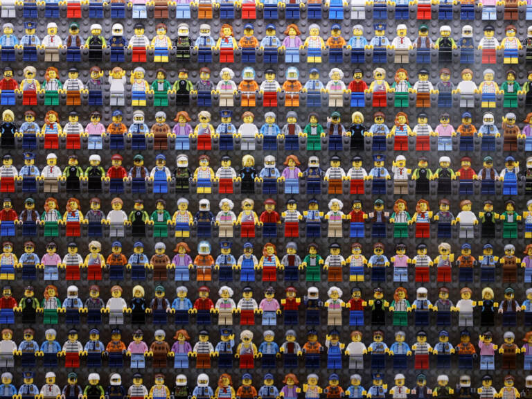 A wall of LEGO minifigures is encased inside the lobby of the LEGOLAND New York Hotel