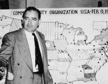 Sen. Joseph McCarthy, R-Wis., testifies during hearings in Washington, D.C., on June 9, 1954. McCarthy stands before a map that charts alleged communist activity in the United States. (Getty Images)