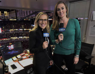 Kate Scott, left, and AJ Mleczko stand holding mics in a sports booth