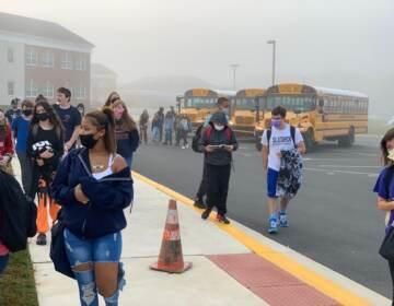 Students, wearing masks, walk into school