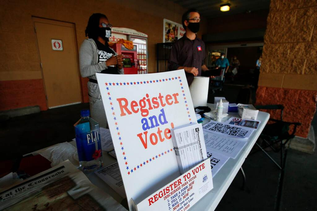 """Two people stand by a table with a sign that reads, """"Register and vote."""""""