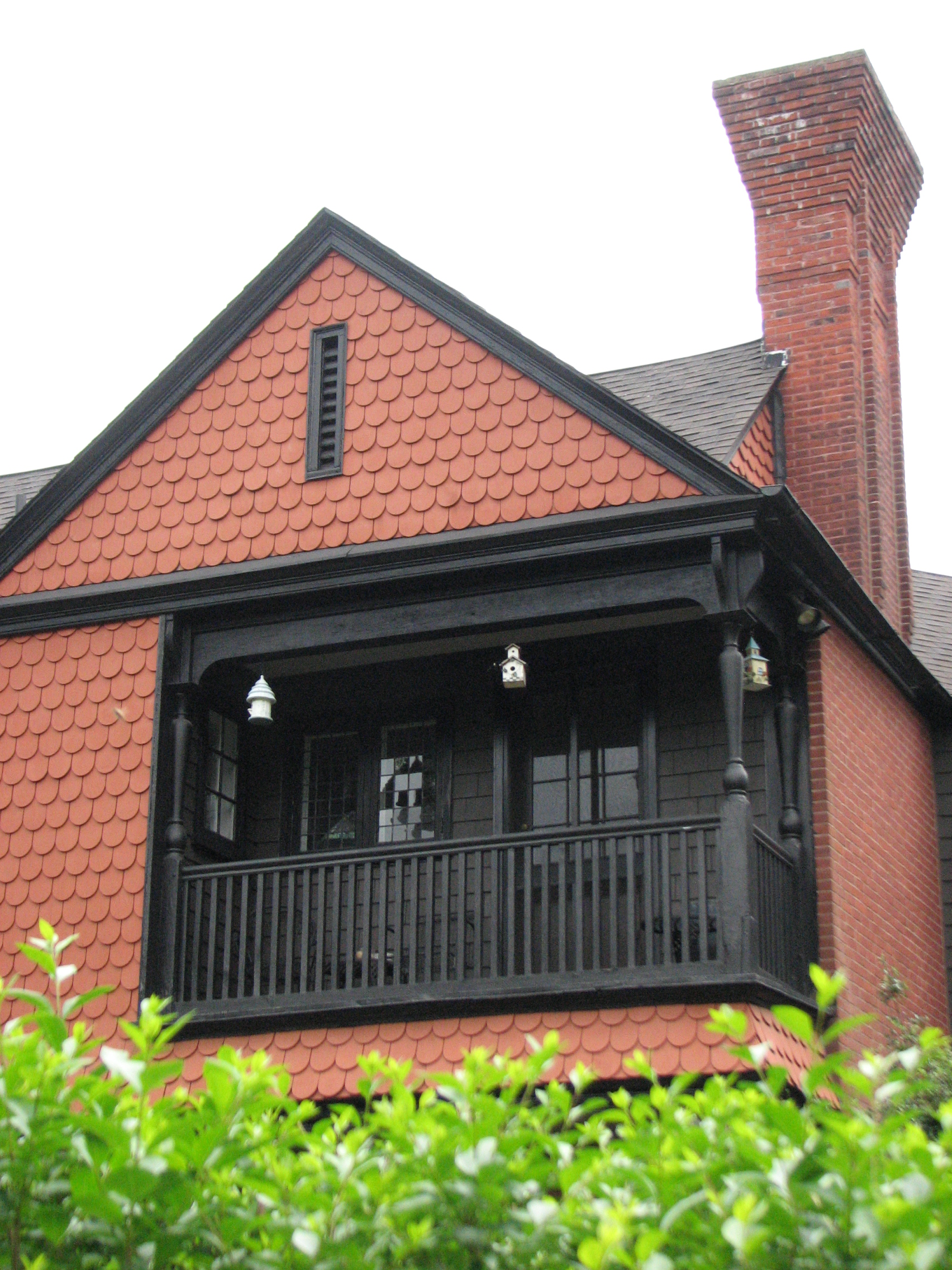 A corbelled chimney and shingle skin surround a third-floor balcony.