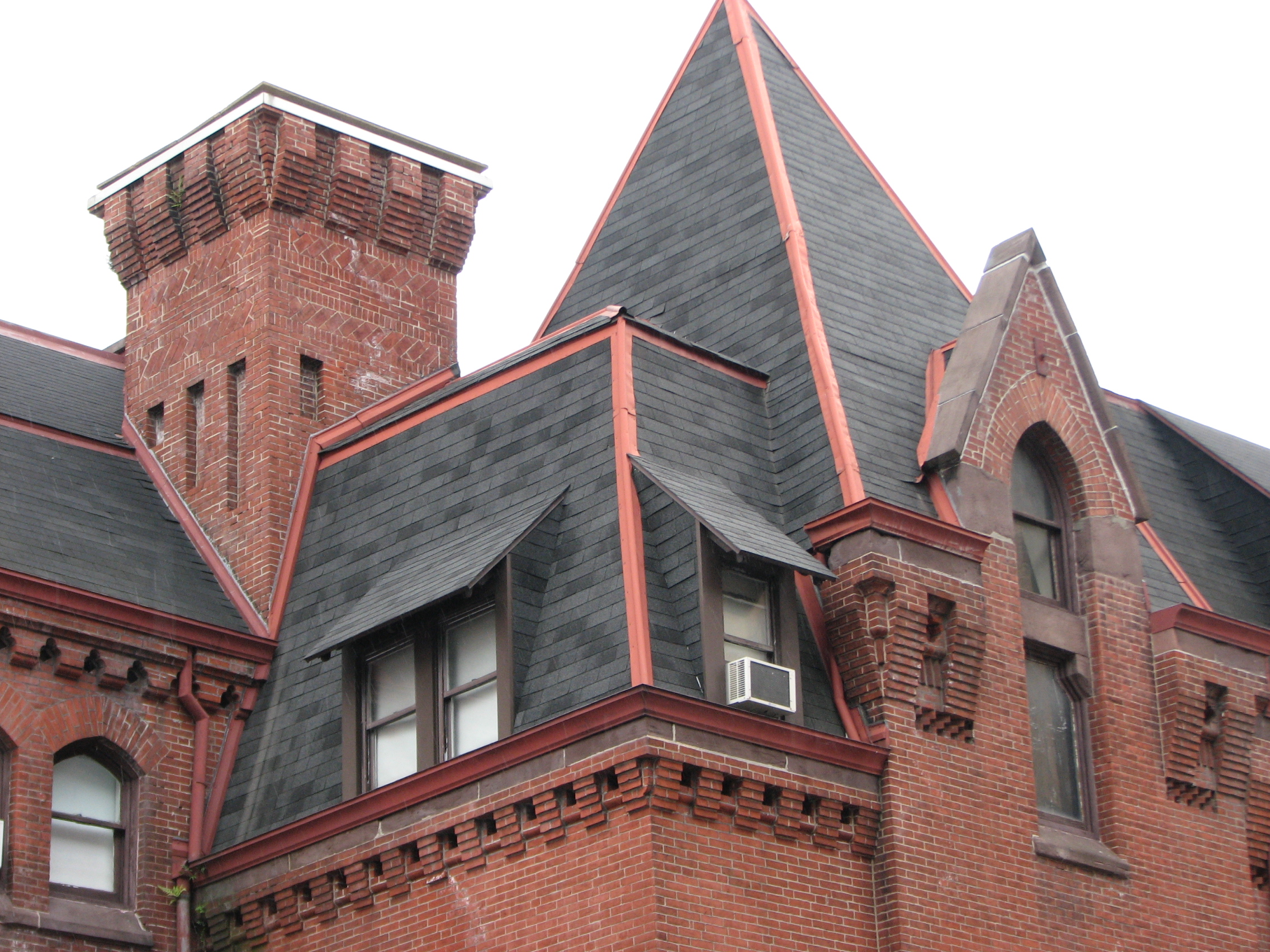 Pitched roofs, gables, dormers, and corbelled chimneys adorn the sections designed by Furness.