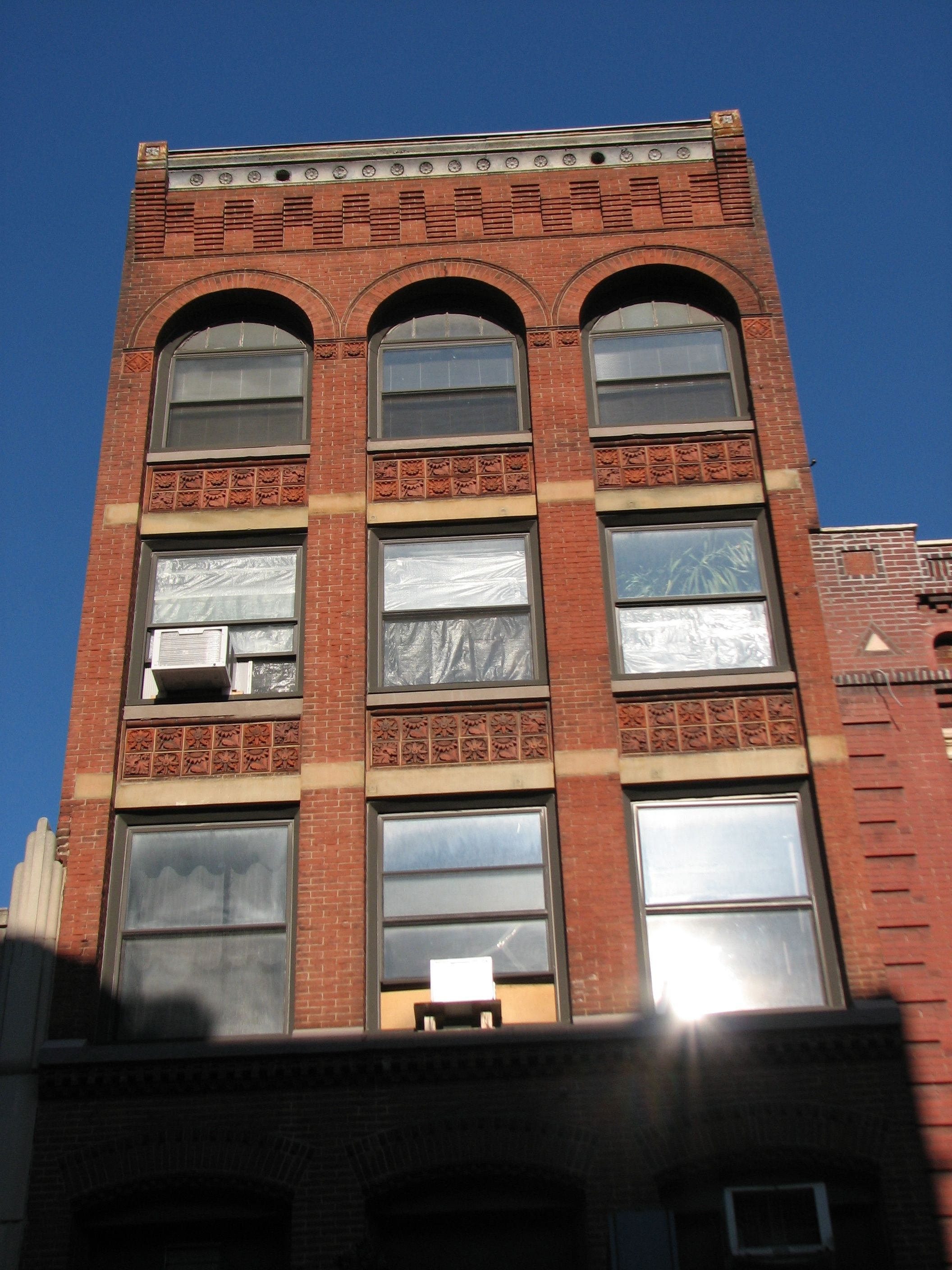 A commercial building on Sansom's north side features terra cotta tiles and corbelled brick.