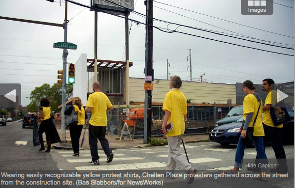 Wearing easily recognizable yellow protest shirts, Chelten Plaza protesters gathered across the street from the site