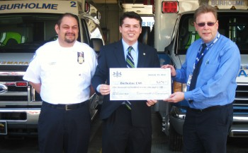 Responder Lou Maldonaldo (L) and BEMS Managing Director Tim Hinchcliff (R) accept a check from Rep. Brendan Boyle and the state. Photo/G.E. Reutter