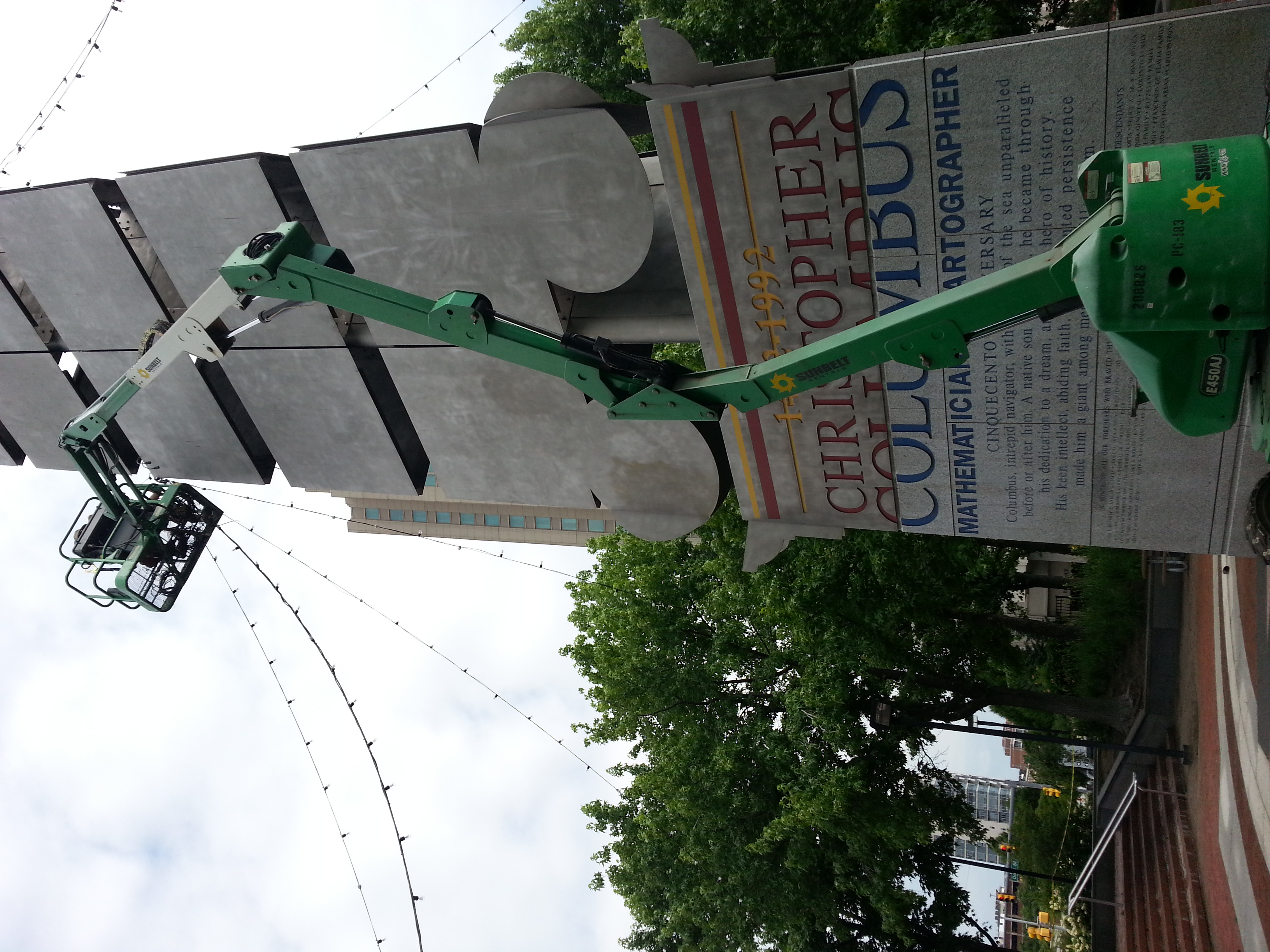 Market lights being strung at the Christopher Columbus monument for Spruce Street Harbor Park