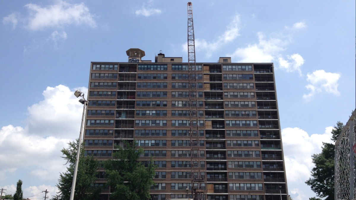 Activity at the Queen Lane Apartments site now sees a crane standing taller than the high-rise building. (Brian Hickey/WHYY)