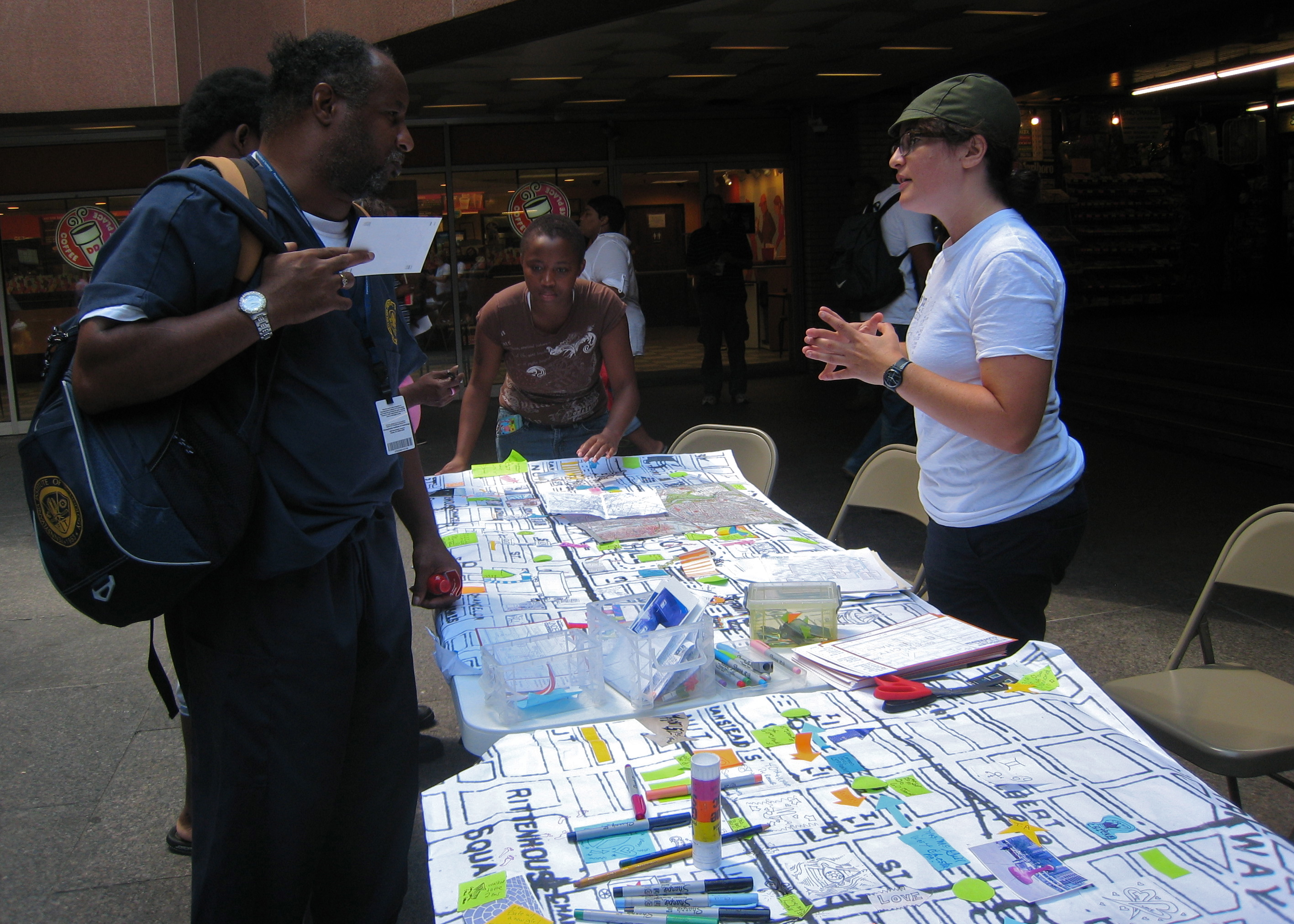 (Miriam Singer (right) talking to people passing through Centre Square's subway concourse entrance, asking them to add their routes and stories to the big map.)