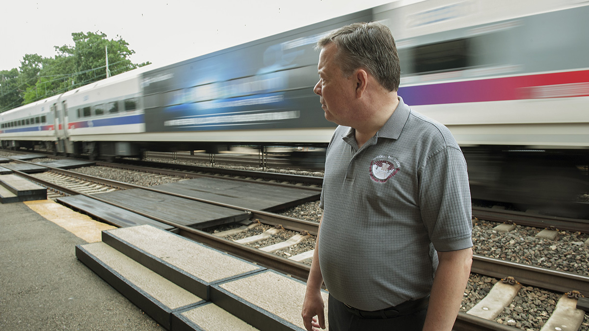 Ardmore Station Ticket Agent Bill Cairns watches a SEPTA train bypass the station. Some trains bypassed the station because they were already full to capacity. (Jonathan Wilson for Newsworks)