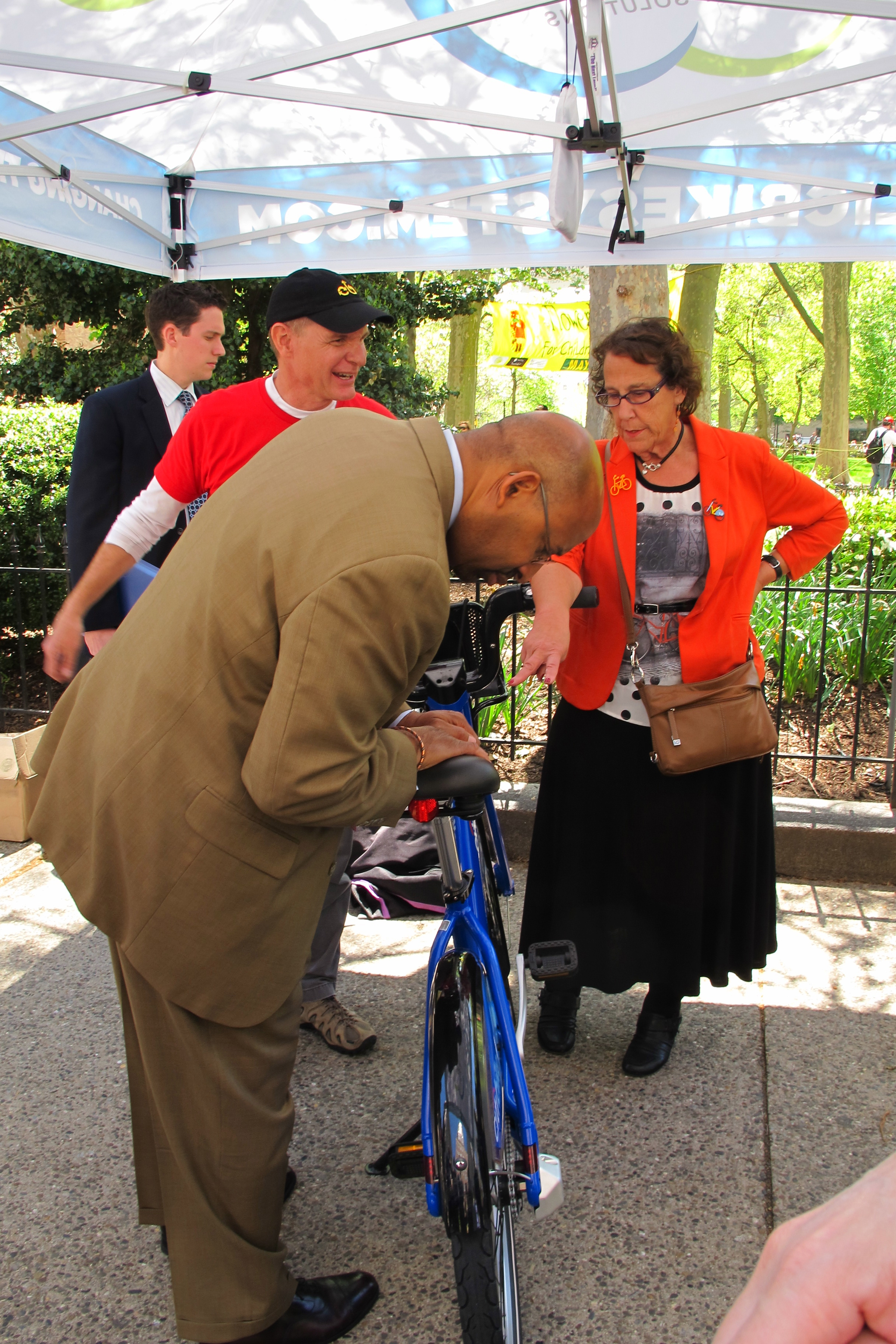 Mayor Michael Nutter, Deputy Mayor Rina Cutler kick the tires as Alta's Charlie Denney explains their system and bikes.