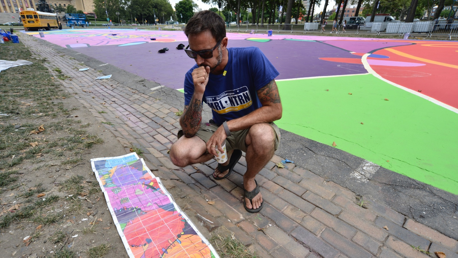 Lead muralist Brad Carney checks the design of his 25,000-square-foot mural 'Rhythm & Hues', that is currently being painted at Eakins Oval. (Bastiaan Slabbers for NewsWorks)