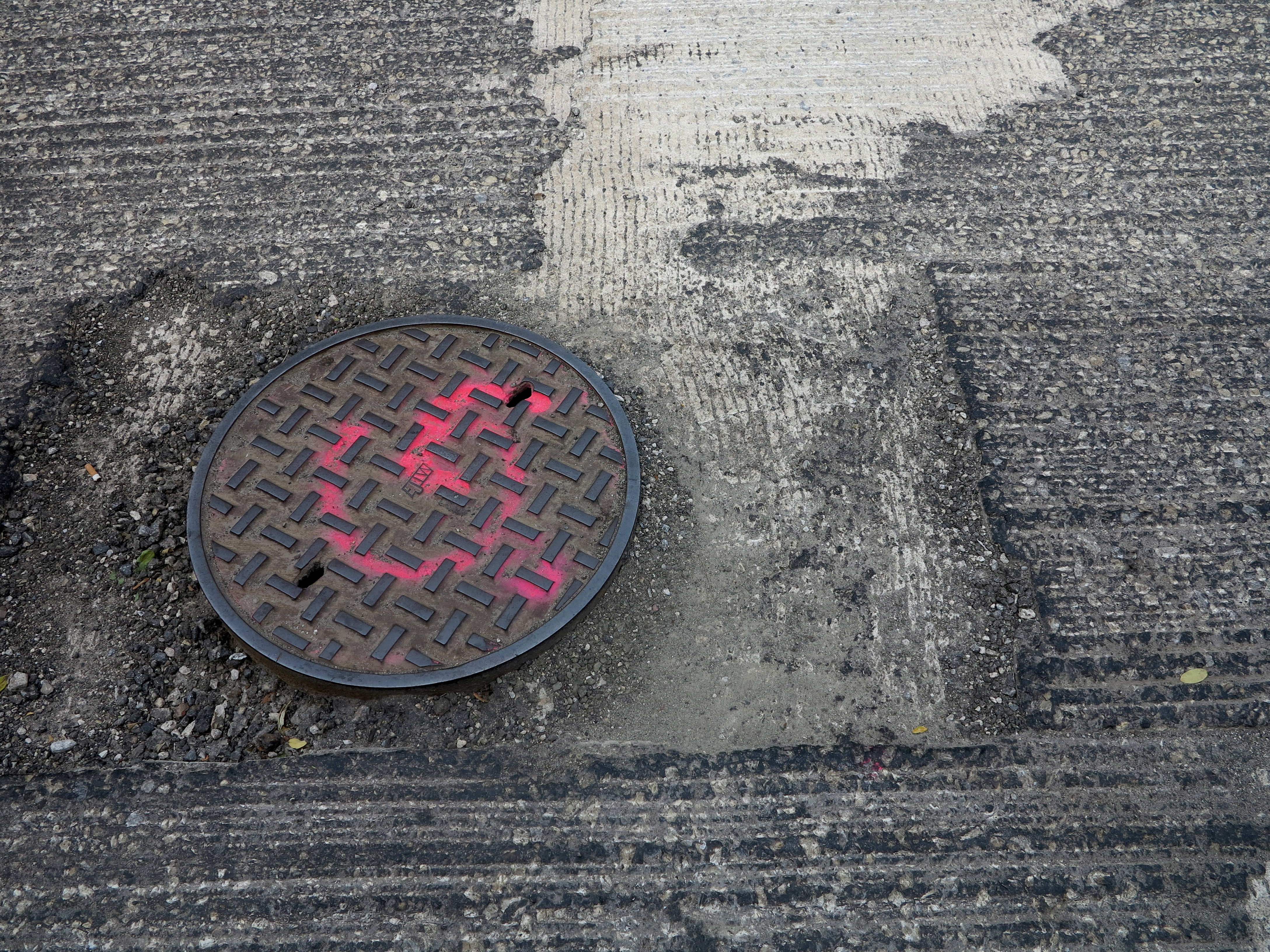 Manhole covers will be reset before resurfacing.
