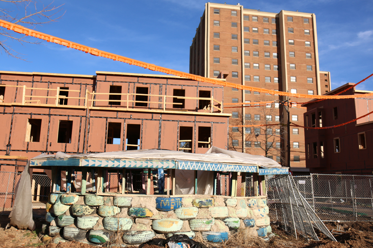 This spring, the Peace Park's schoolhouse still stood behind the agency's new apartments and in the shadow of the public housing towers. (Marielle Segarra/WHYY)
