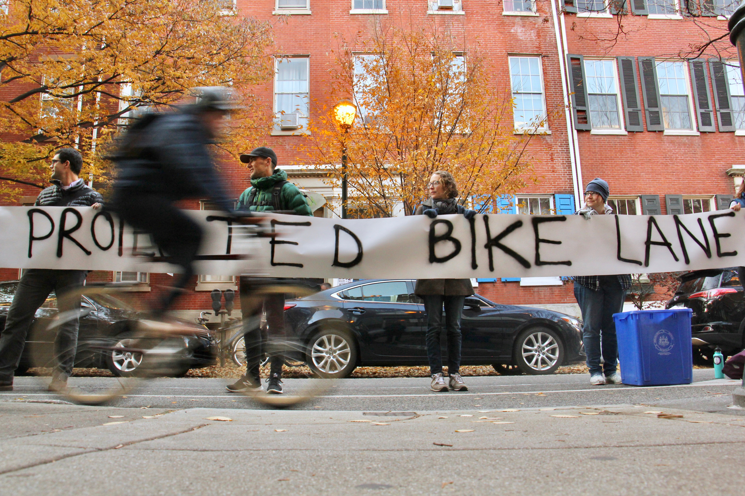 Bicyclists forming a human-protected bike lane hold up a banner calling for protected bike lanes near site of a fatal crash the day prior