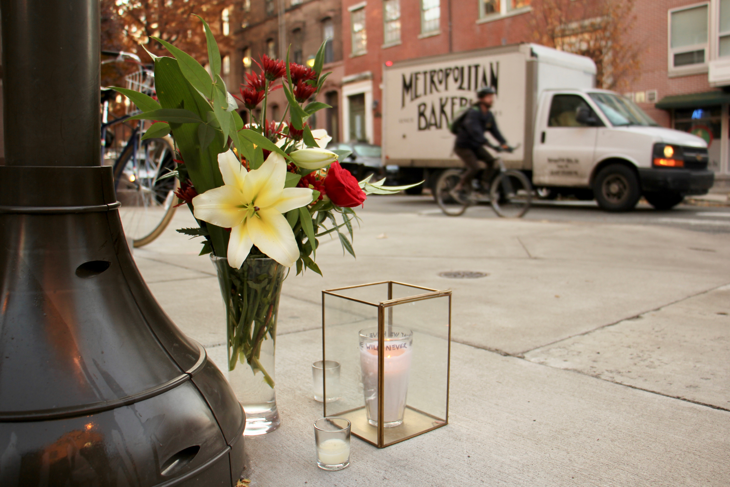 Flowers and candles left at the intersection of Spruce and 11th streets, where cyclist Emily Fredericks was struck and killed (Emma Lee, WHYY)