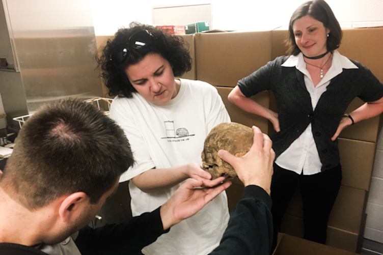 Jared Beatrice (L), Dhody (center), and Kimberlee Moran meet at Moran's lab at Rutgers-Camden to review some of what was excavated from 218 Arch Street in Philadelphia last month. (Elana Gordon/WHYY)