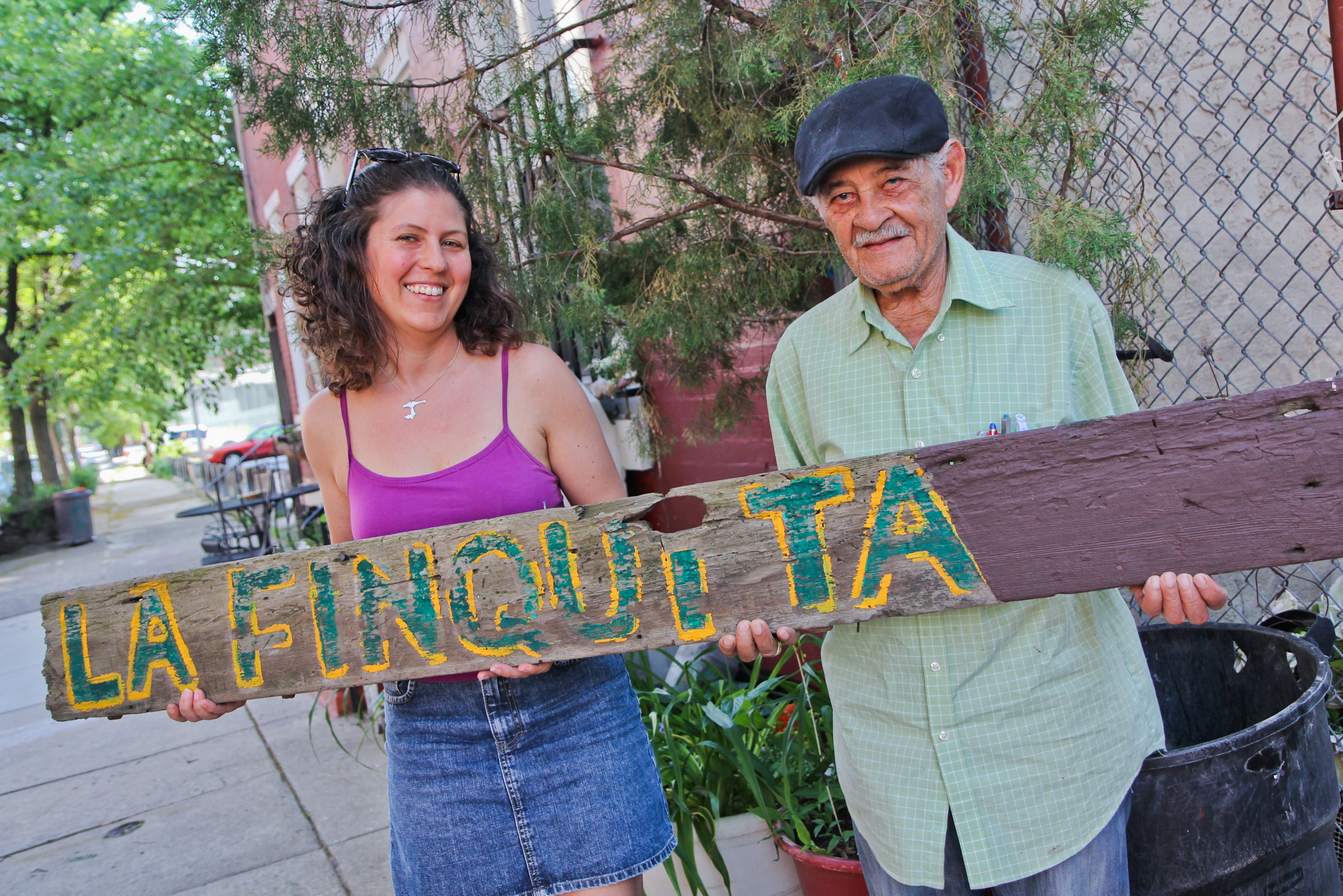 Jessica Noon and Daniel Rodriguez holds the hand-painted sign that remains from the now-departed La Finquita at Lawrence and Master streets.