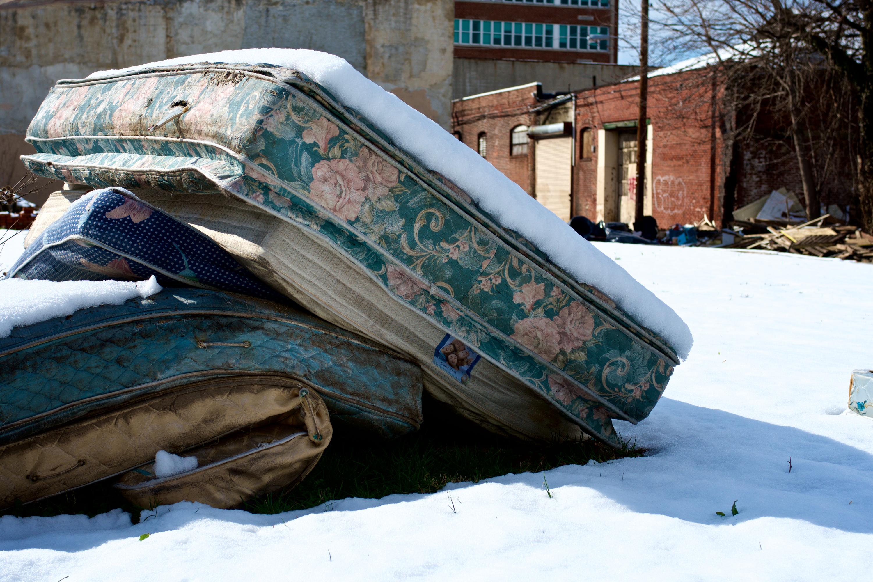 Mattresses piled up in a vacant lot. (Bas Slabbers/WHYY)