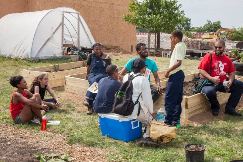 Maya Thomas (left) sits on a raised planter bed in North Philadelphia Peace Park
