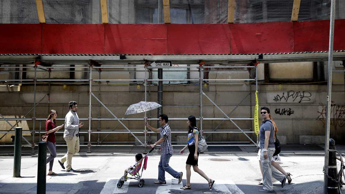 People cross a street near a construction site on Market Street in Center City, Philadelphia. (AP Photo/Matt Rourke)