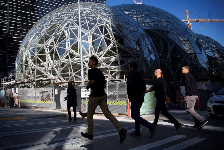 People walking in the shadow of Amazon's headquarters in Seattle. (Megan Farmer/KUOW)