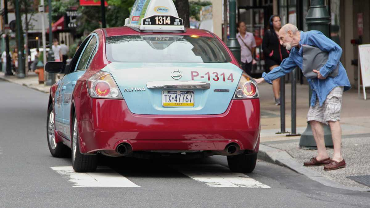 A taxi cab picks up a passenger in Philadelphia. (Emma Lee / WHYY)