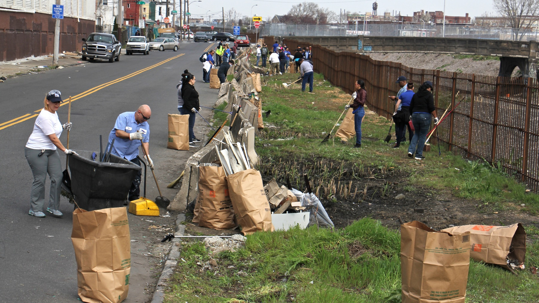 Workers and volunteers clean up trash in preparation for a new greenway alongside the former site of a notorious Kensington heroin encampment. (Emma Lee/WHYY)