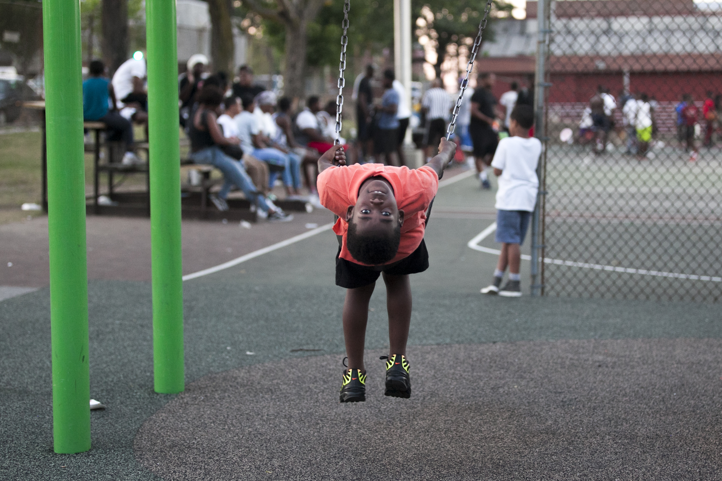 A young Philadelphia looks backwards from his swing at Dendy Playground on the evening of Wednesday, July 18, 2018. | Maggie Loesch for PlanPhilly
