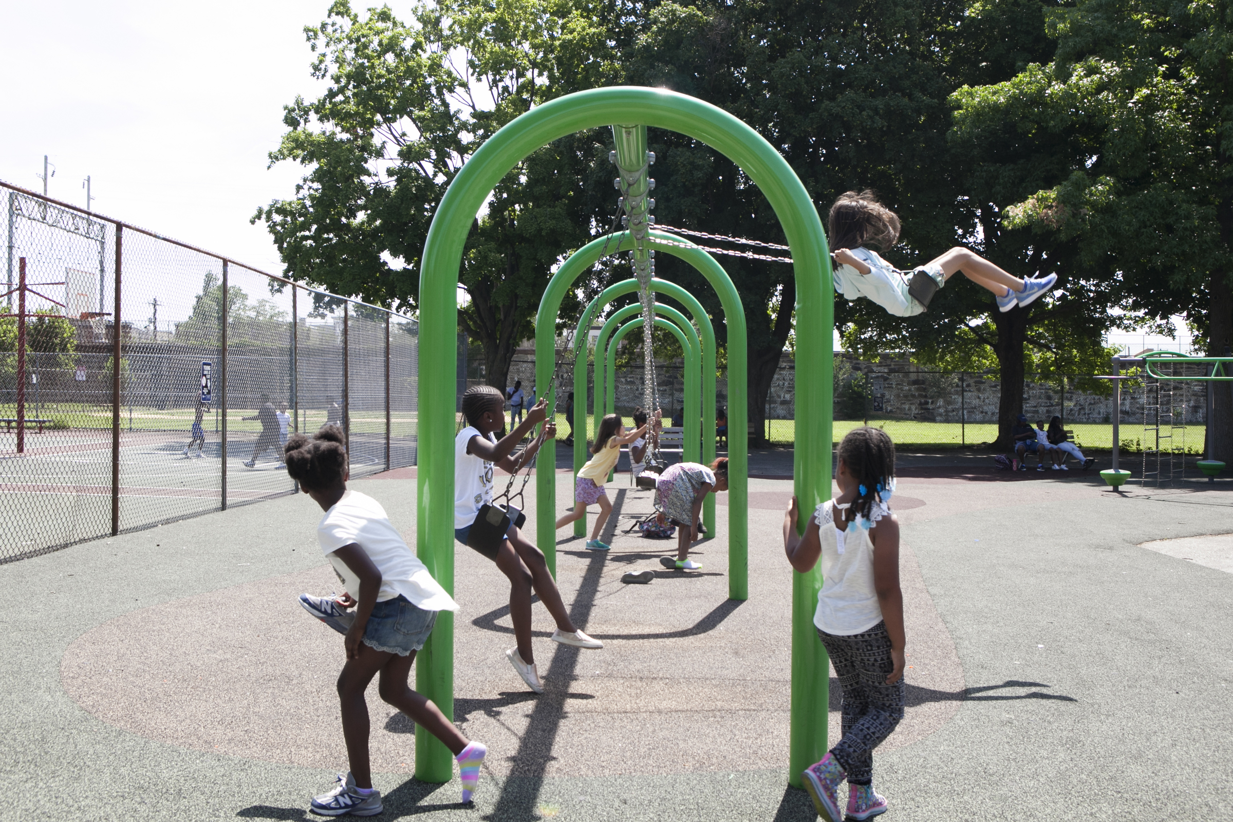 Camp kids play on the swings on the morning of June 29. | Maggie Loesch for PlanPhilly