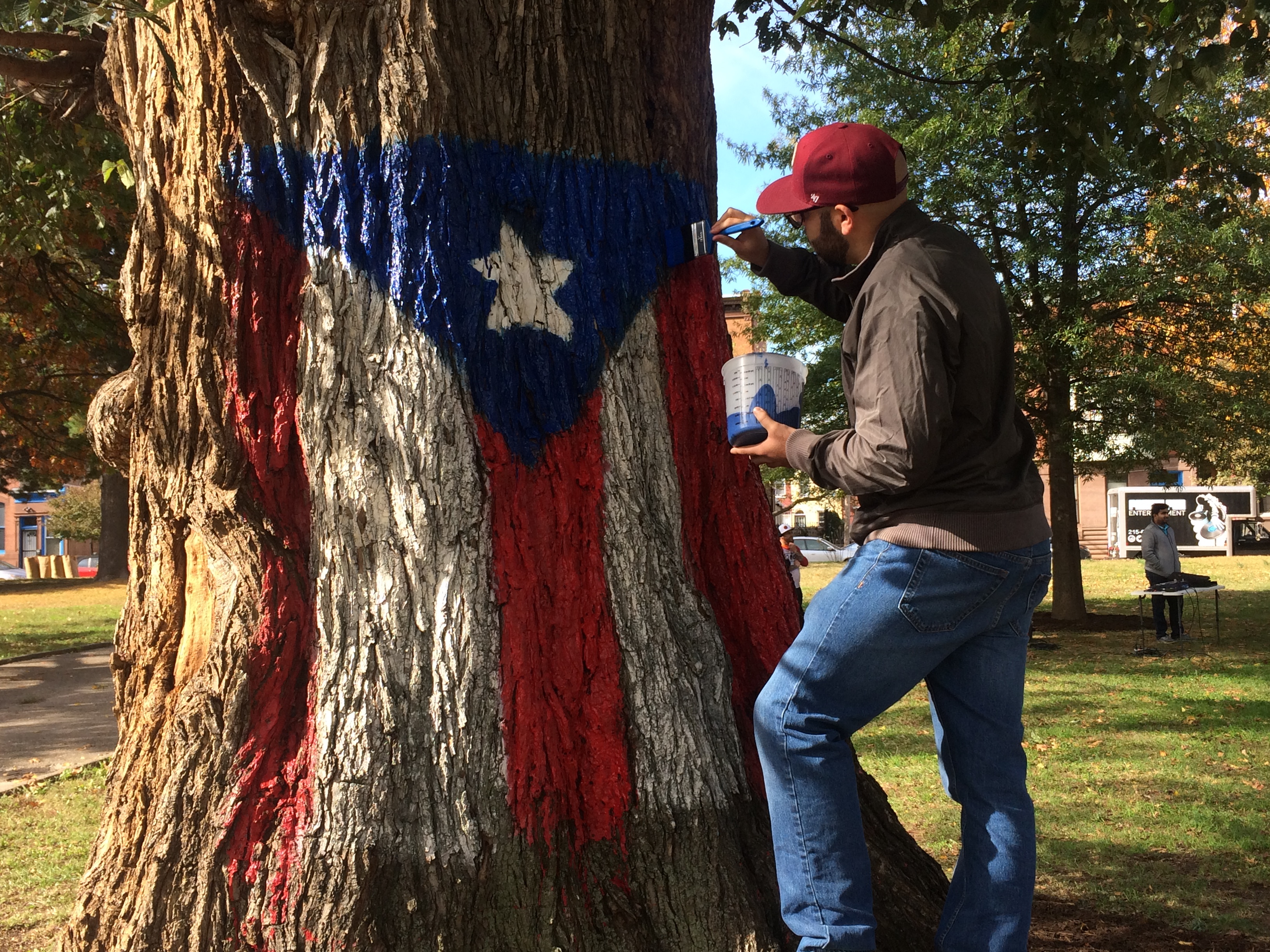 Philadelphia is actively helping rebuilt Puerto Rico. In the picture, man retouching Puerto Rican flag in Norris Square Park.
