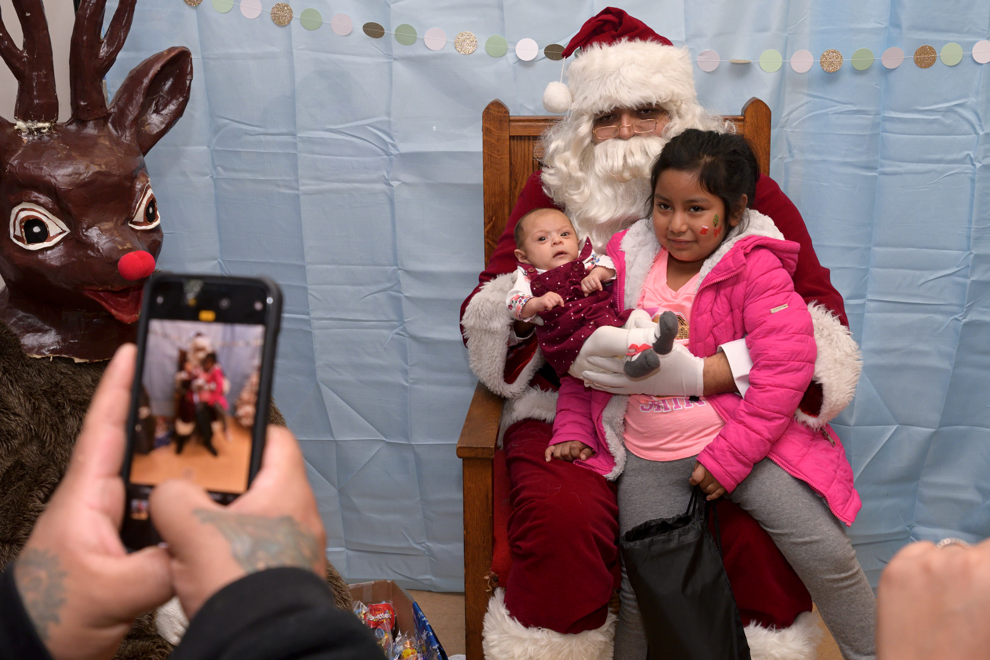 Kids pose for a picture with Santa and Rudolph at the Annual Winter Festival in Olney. Bas Slabbers/WHYY.