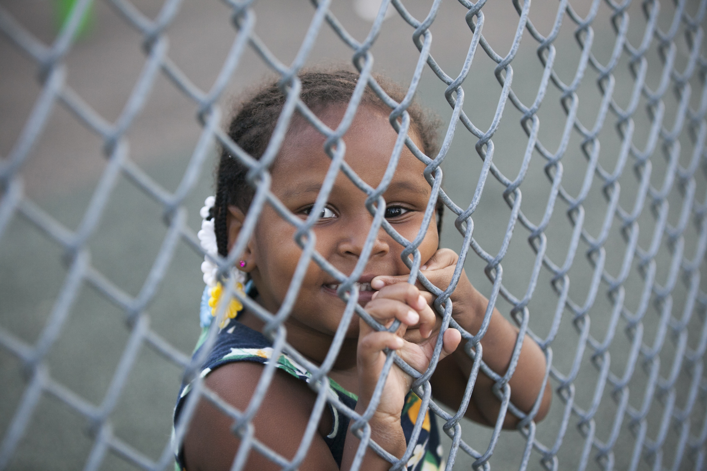 Mimi, 2, peers through the fence separating basketball courts from the play equipment at Dendy. | Maggie Loesch