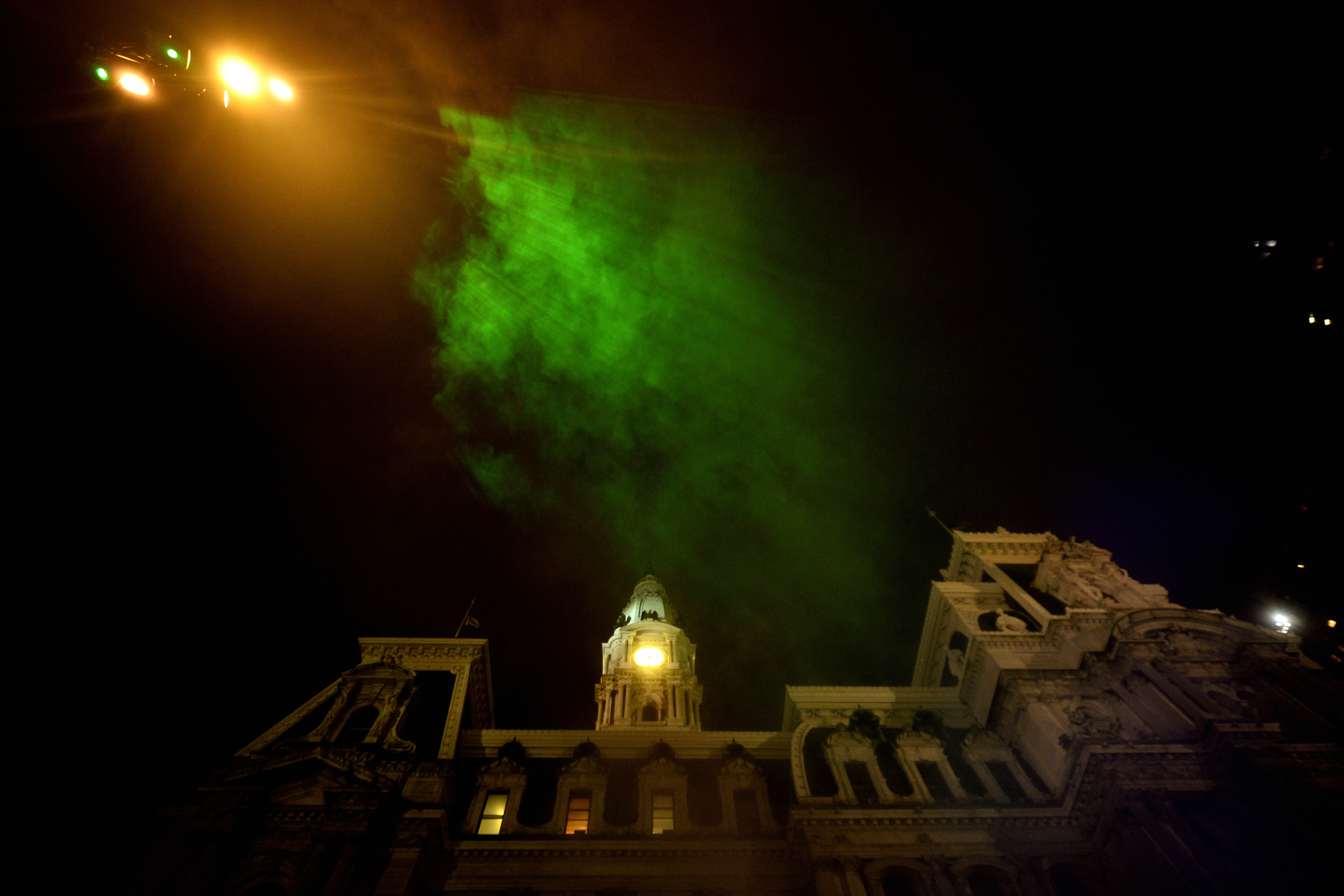 Mist catches green rays of light as it billows up towards the sky during the public unveiling of the first section of the site-specific art installation titled Pulse at the Dilworth Park's fountain, on Wednesday. (Bastiaan Slabbers for WHYY)