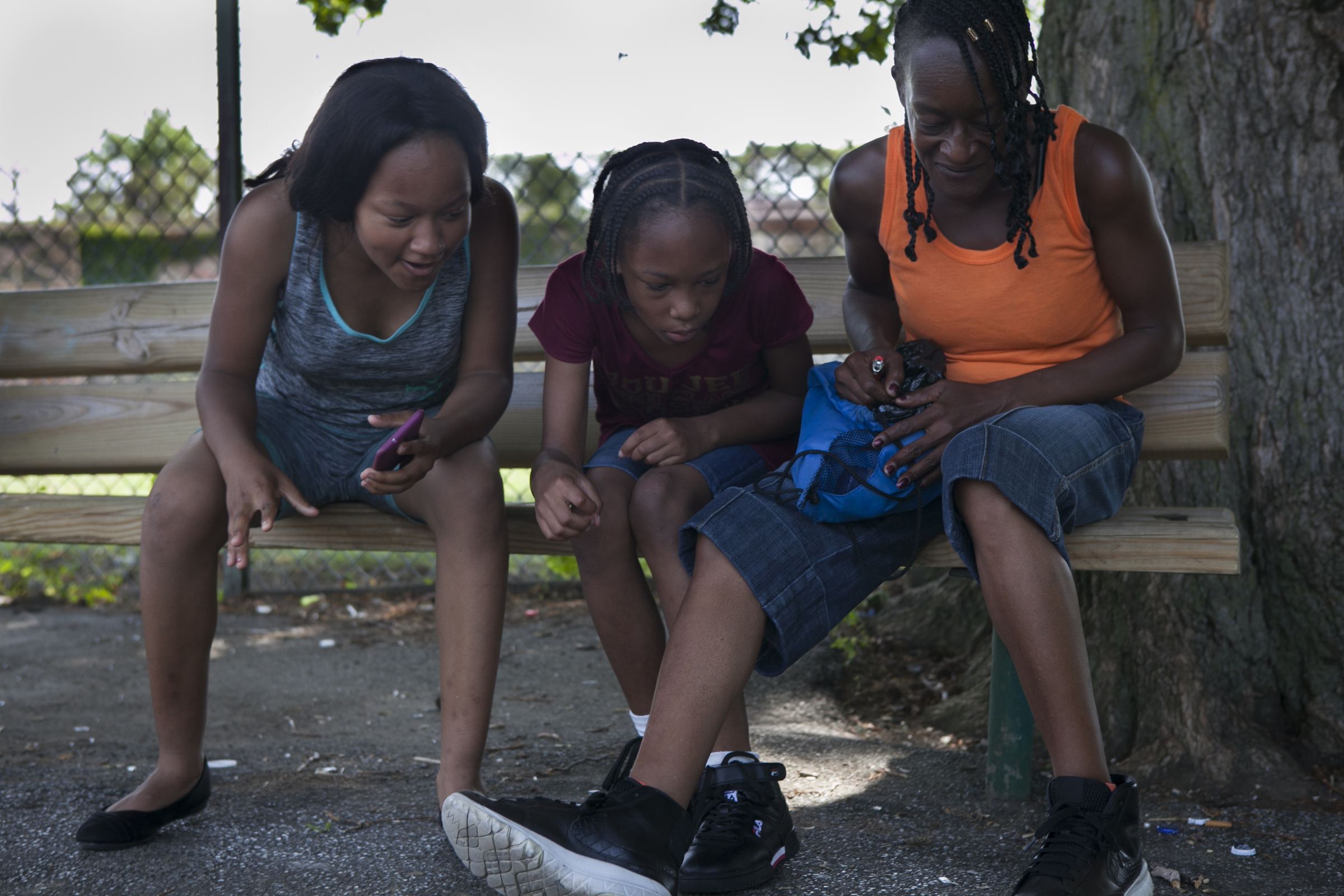 Sisters Savannaha Marion, 15, Cionne Richardson, 13, and their mother Michelle Richardson, all of Strawberry Mansion, look at a caterpillar on the blacktop at Dendy Playground on the morning of Friday, June 29, 2018. MAGGIE LOESCH