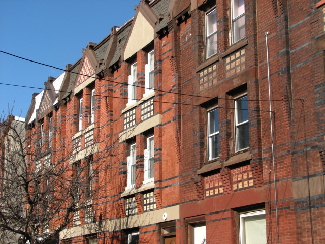 A row of 19th century houses at 1821-1833 Thompson St. is distinguished by the elaborate brickwork and terra cotta insets.