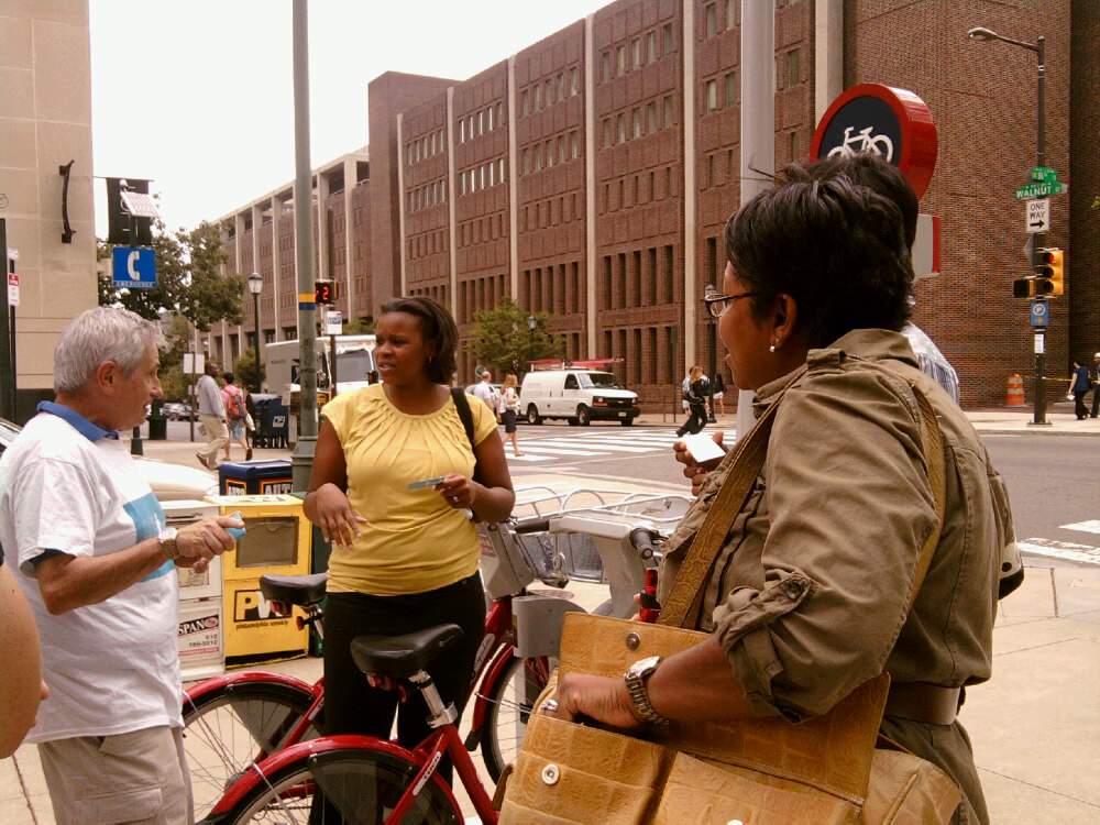Lakeisha Bishop, Bonny West and Serita Lewis (behind West) talk to Russell Mendin about bike share