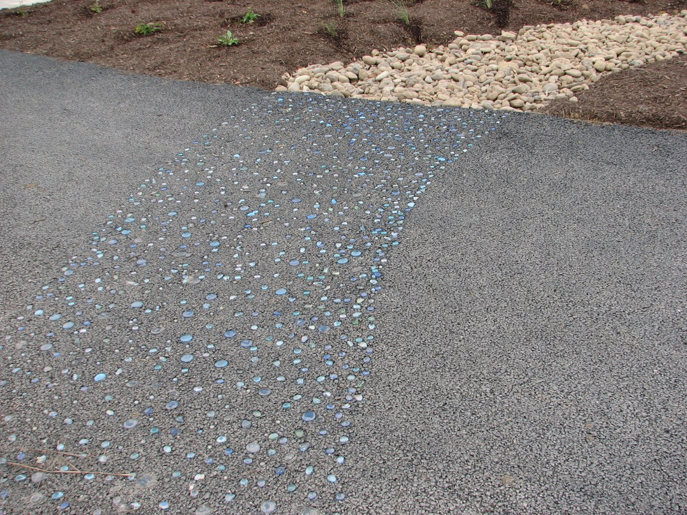 The blue glass stones embedded in the trail suggest water