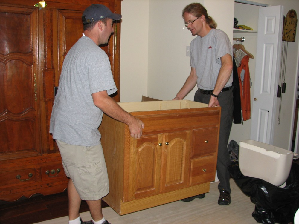 Donor Johannes Reiser helps volunteer Don Liberati move a bathroom vanity