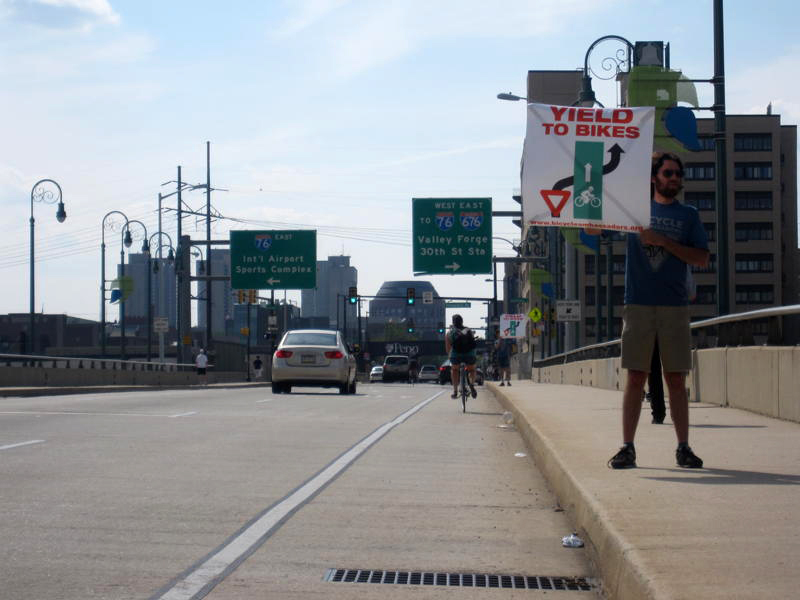 Ambassador Julian Root holds up a sign on the Walnut Street Bridge urging cars to yield to bikes.