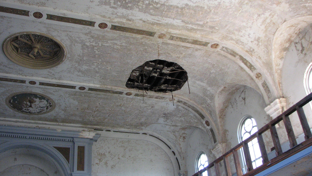 Holes scar the once-ornate ceiling.