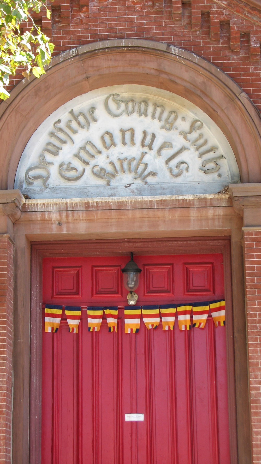 Flags of the new congregation now hang below the original German inscription on the building entrance.