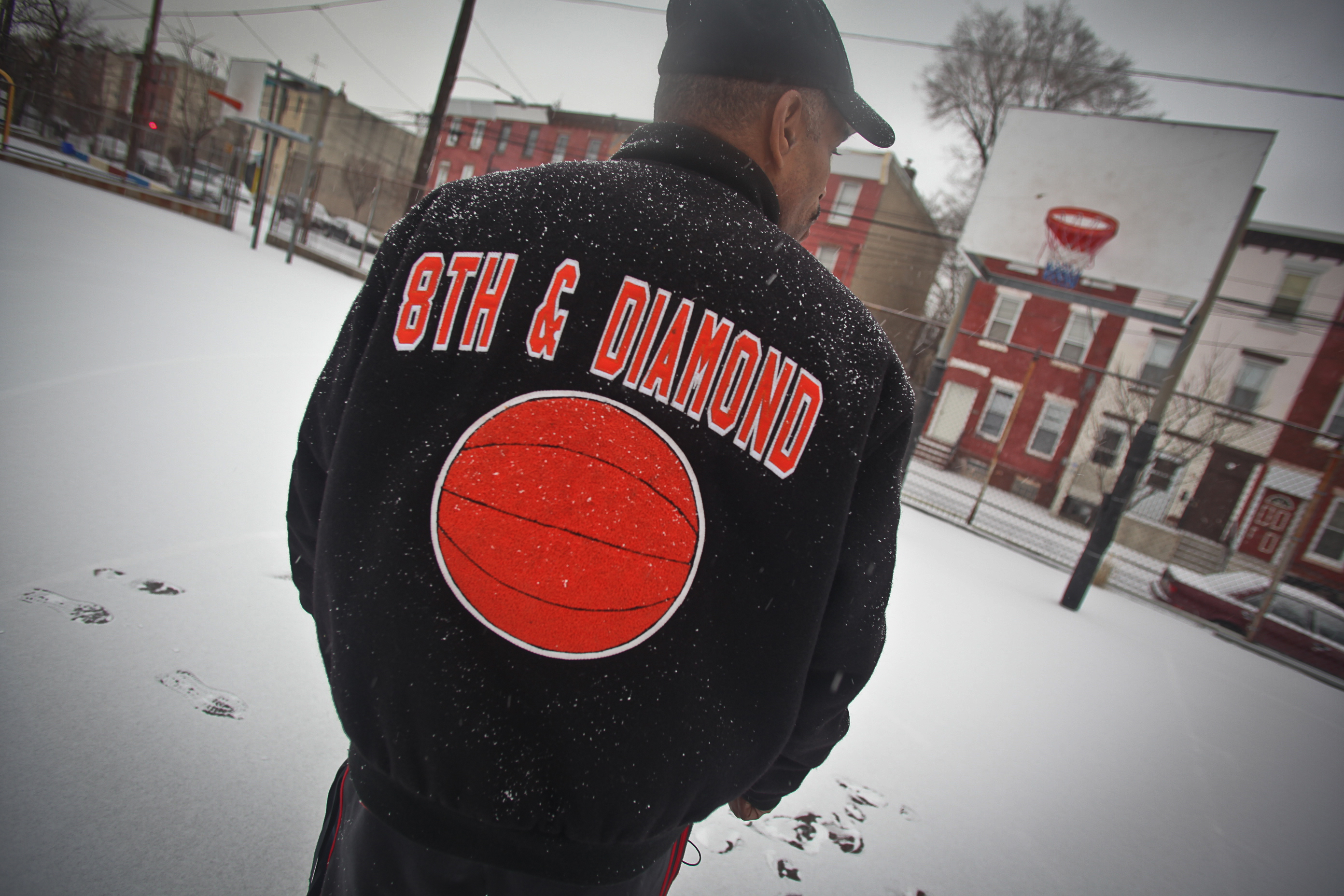 Dana Clark, the director of the 8th and Diamond playground, walks through a snowy basketball court.
