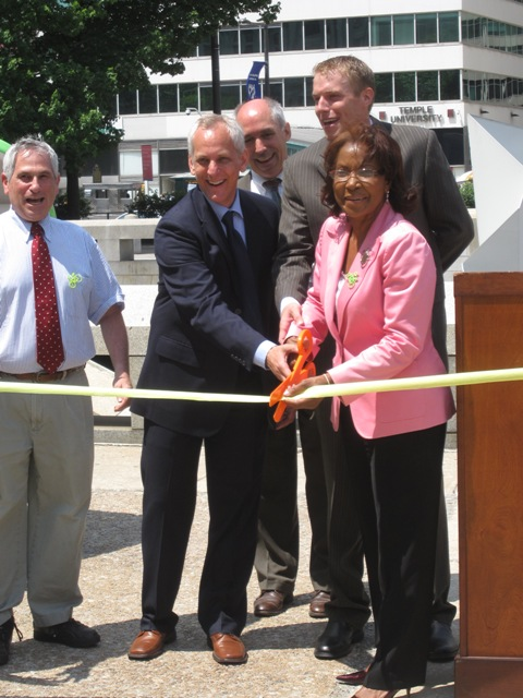 Ash, Dambman, and Reynolds Brown, joined by others who helped in achieving the new legislation, cut the ribbon