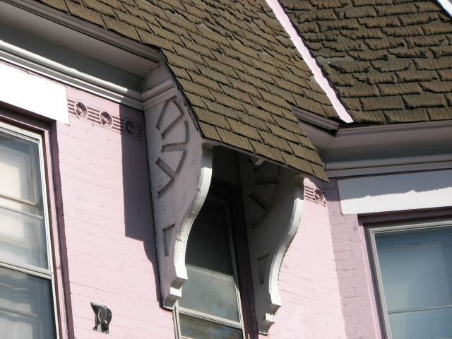Incised brackets adorn upper windows of a few homes.