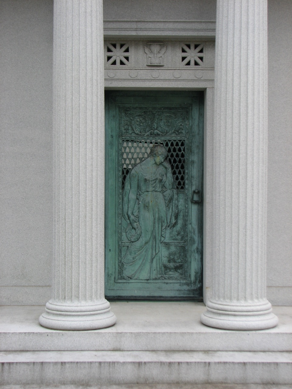 Classical columns and the figure of a woman adorn the entrance to a turn-of-the-century mausoleum.