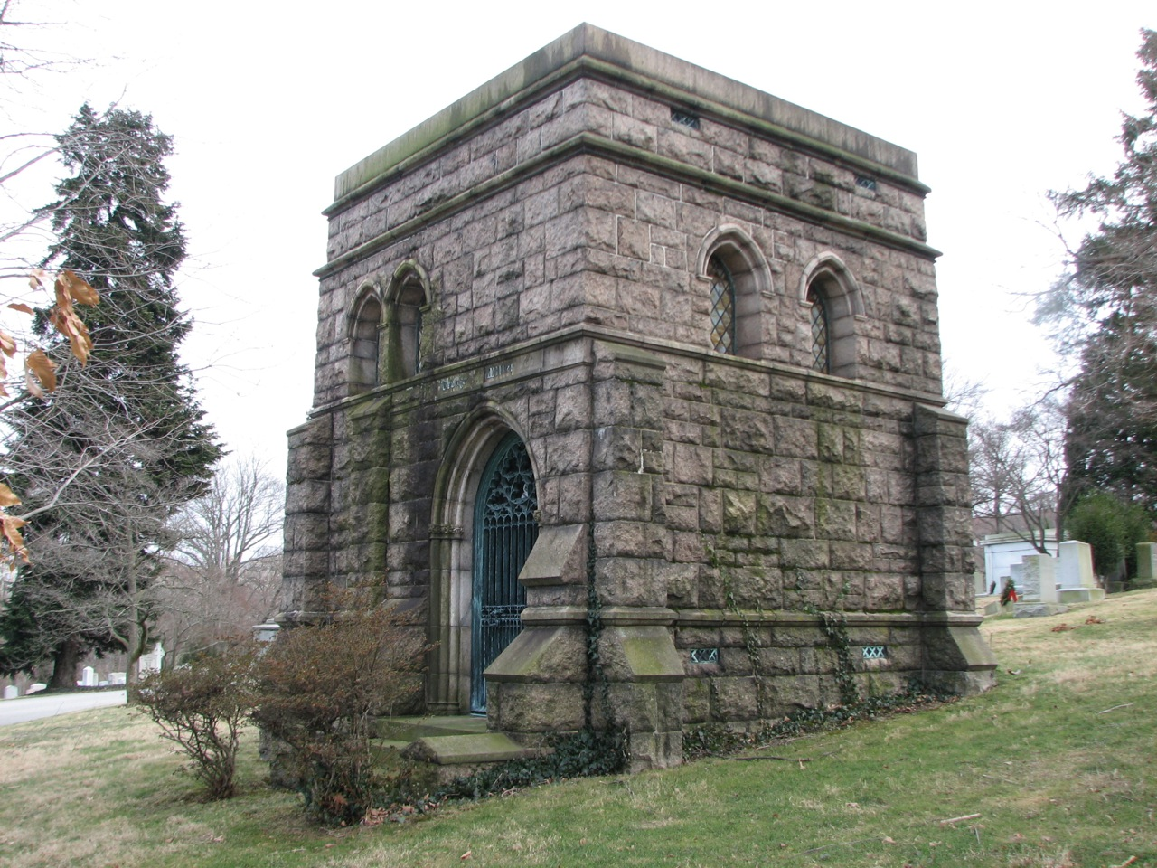 A tomb of rough-hewn stone resembles a Gothic castle.