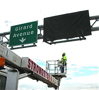 PennDOT worker installing the new Girard Ave signs. (PennDOT photo)