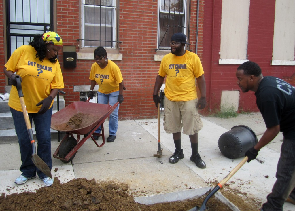 Catalyst for Change Church members Janice Niangane, Tracey Dickerson, Eric Pierce and Pastor Keon Gerow prepare a hole in the sidewalk for planting.