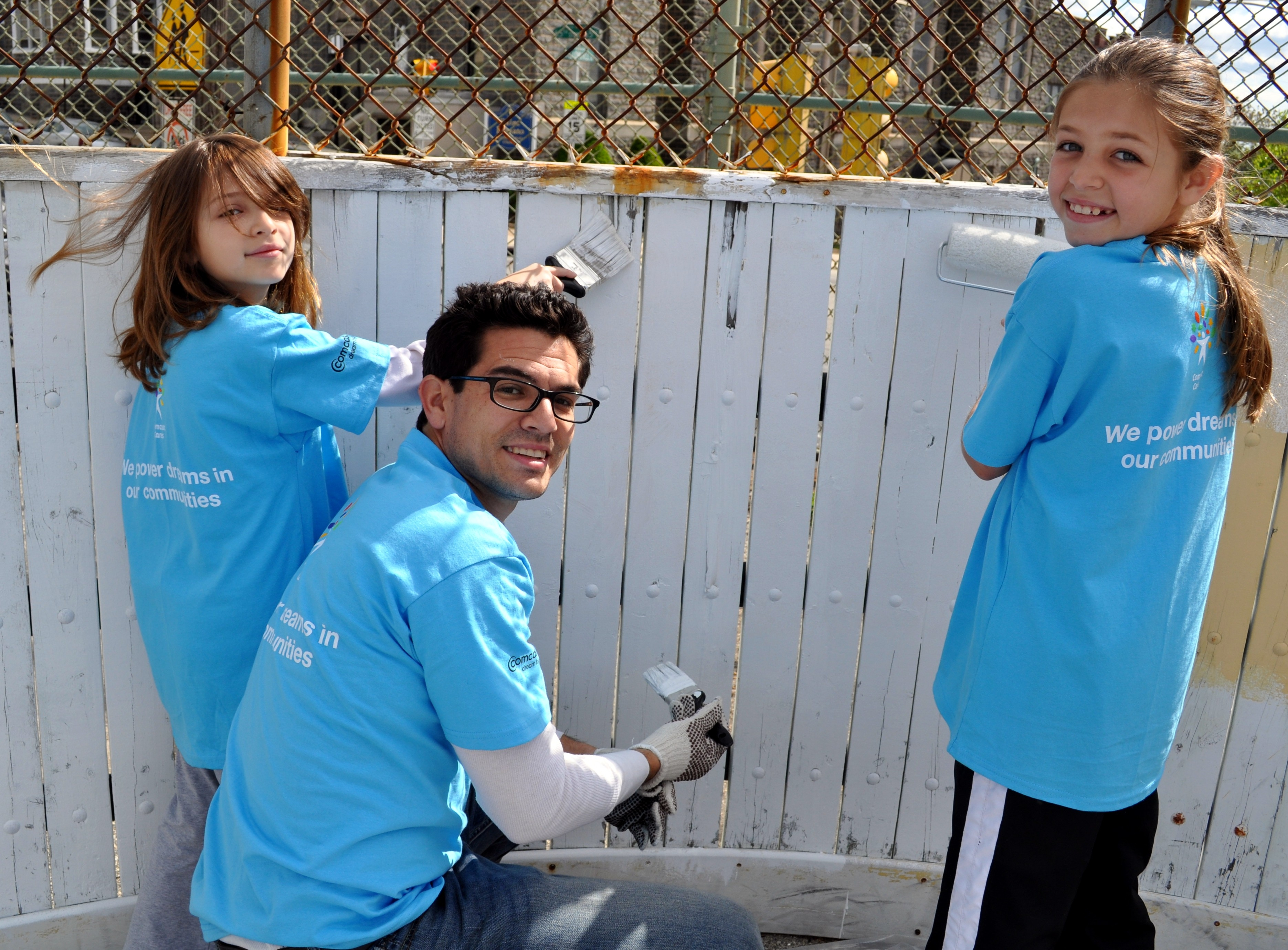 Comcast employee Joshua Palau and his daughters Logan (L) and Zoe (R) paint a fence at the Granahan Recreation Center in West Ph